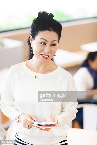 Senior Asian Woman Passing By In A Cafeteria