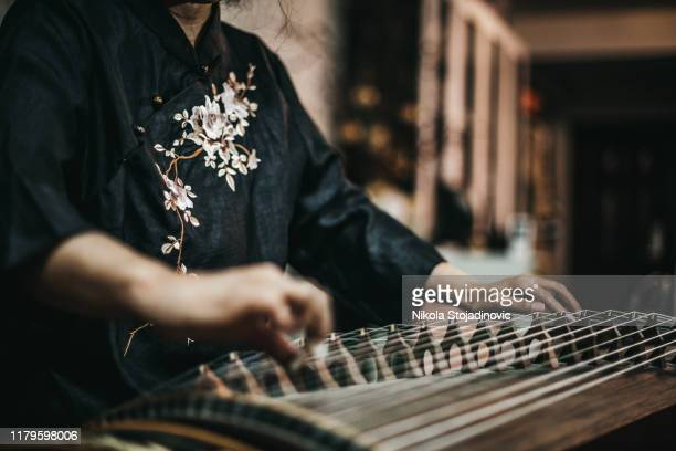 senior asian woman playing - traditional clothing stock pictures, royalty-free photos & images