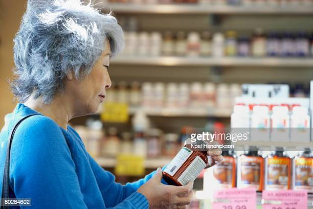 senior asian woman reading vitamin label - nutritional supplement stock pictures, royalty-free photos & images
