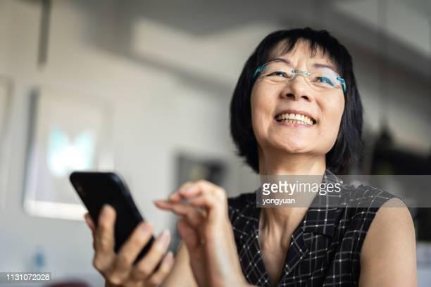mulher asiática sênior que usa um smartphone - 60 64 anos - fotografias e filmes do acervo