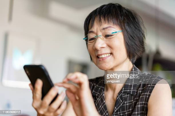 senior asian woman using a smartphone - ringing stock pictures, royalty-free photos & images