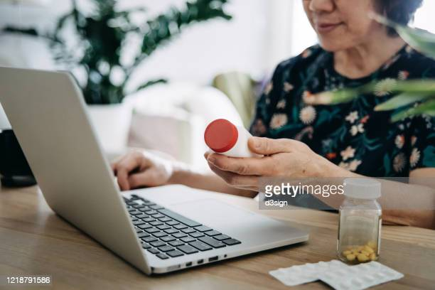 senior asian woman video conferencing with laptop to connect with her family doctor, consulting about medicine during self isolation at home in covid-19 health crisis - medicare stockfoto's en -beelden