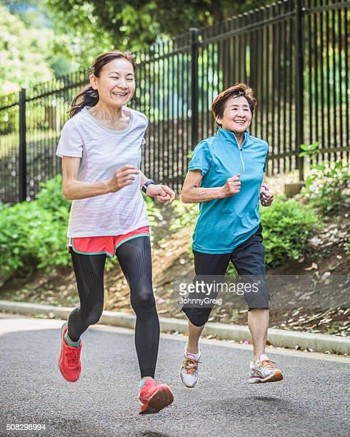 アジアの老人女性のジョギングを一緒に公園に、笑顔