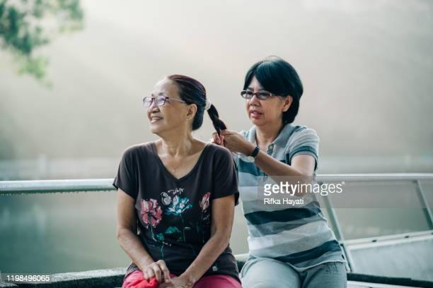 senior asian women tying friend's hair - rifka hayati stock pictures, royalty-free photos & images