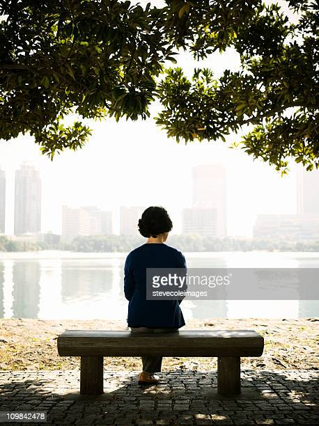 Senior AsianWoman Sitting on a Park Bench