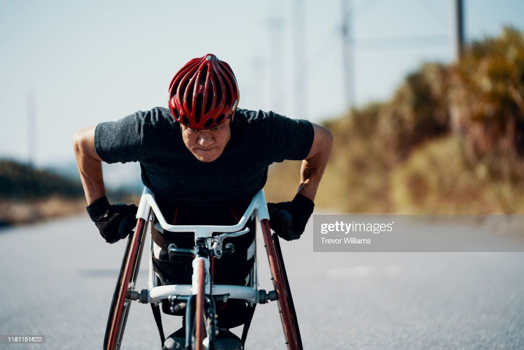 Senior athlete in a racing wheelchair practicing on a rural road. : ストックフォト