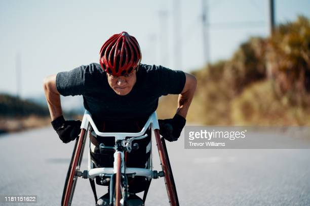 Senior athlete in a racing wheelchair practicing on a rural road.