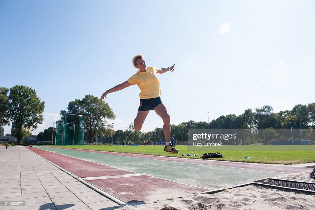 Senior athlete (75) practicing long jump : Stockfoto