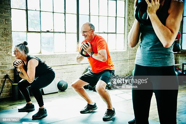 senior athletes doing kettlebell squats - learning objectives stock pictures, royalty-free photos & images