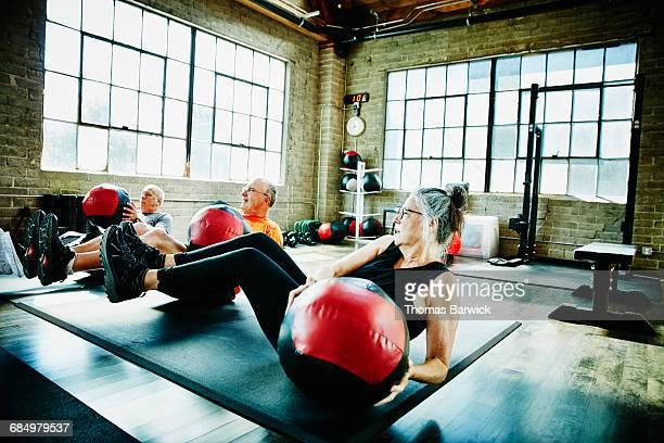 Senior athletes doing medicine ball twists