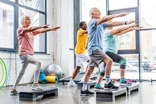 senior athletes synchronous exercising on step platforms at gym 1088958514