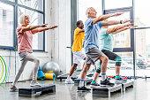 senior athletes synchronous exercising on step platforms at gym