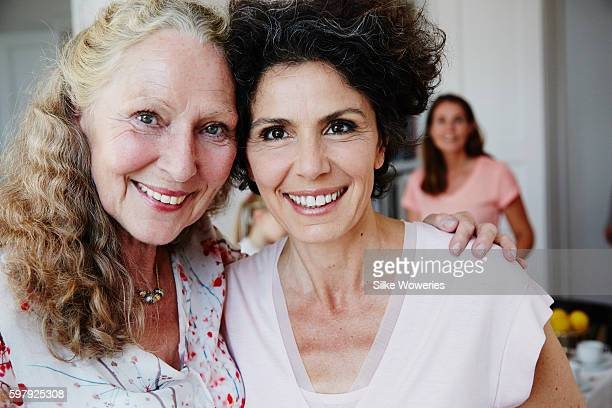 senior aunt embracing her middle-aged niece - aunt stock pictures, royalty-free photos & images