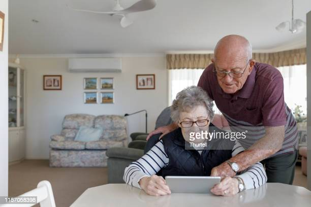 senior australian couple learning to use digital tablet - social security stock pictures, royalty-free photos & images