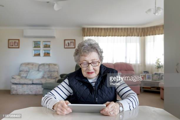 senior australian woman learning to use digital tablet - social security stock pictures, royalty-free photos & images