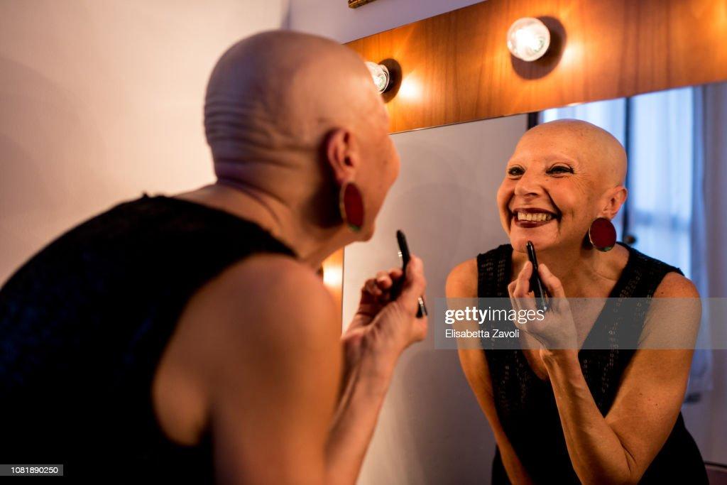 Senior bald woman putting on her makeup : Stock-Foto