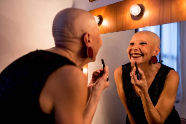 Senior bald woman putting on her makeup
