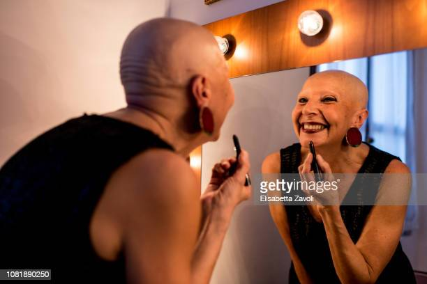 senior bald woman putting on her makeup - showus foto e immagini stock