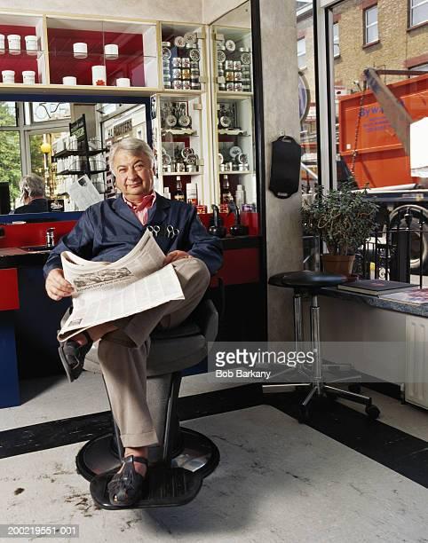 Senior barber relaxing in shop, holding newspaper, portrait