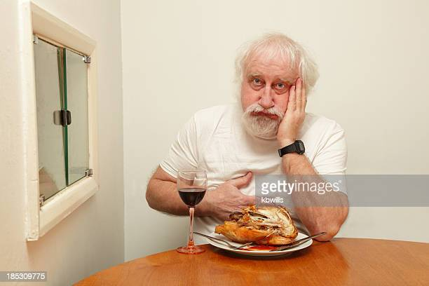 senior bearded male with indigestion after eating roast chicken