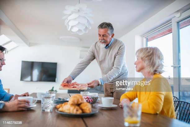 senior bearded man adding charcuterie to his at-home brunch selection - charcuterie board stock pictures, royalty-free photos & images