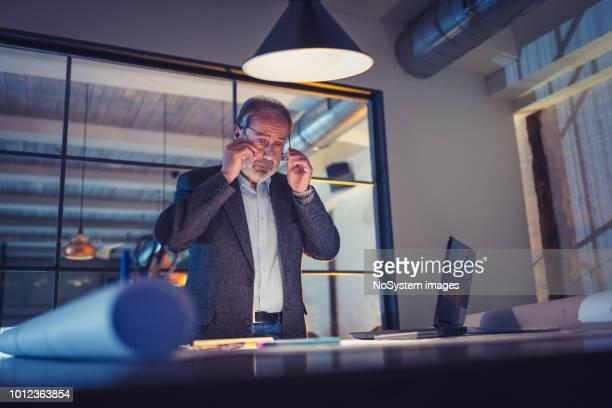 Älteren bärtige Männern Architekt spät im Büro arbeiten
