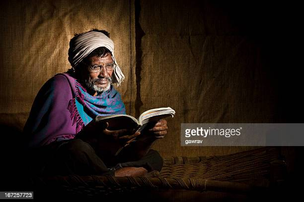 Senior, bespectacled, rural Indian man reading a book