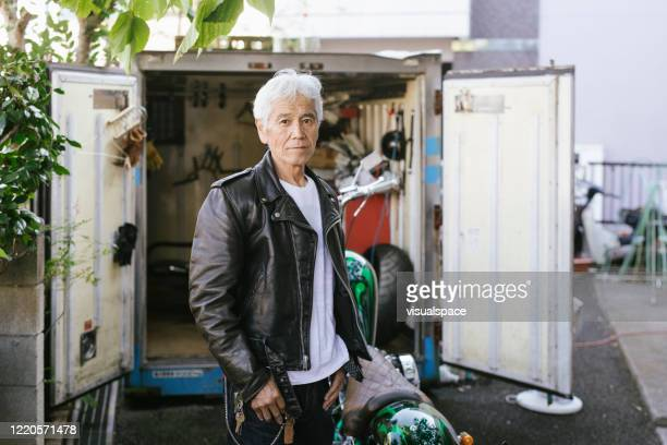 senior biker with motorcycle in front of his garage - biker jacket stock pictures, royalty-free photos & images