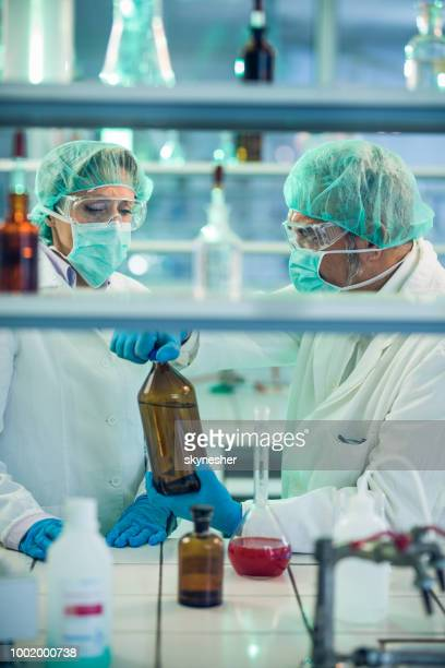 Senior biochemists working with toxic substances in laboratory.