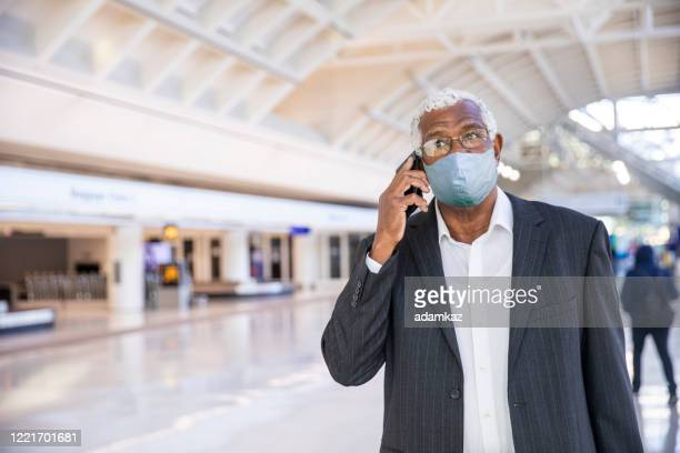 senior black businessman on phone at the airport wearing a mask - adamkaz stock pictures, royalty-free photos & images