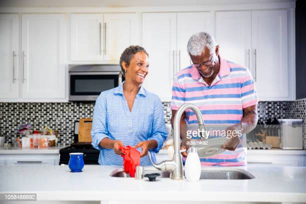 senior black couple doing the dishes - washing up stock pictures, royalty-free photos & images