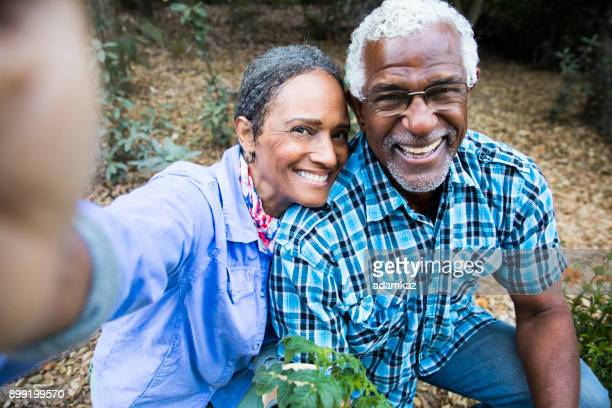 senior black couple gardening taking a selfie - african american couple stock pictures, royalty-free photos & images