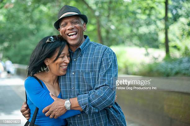 senior black couple hugging and laughing - 50 59 years stock pictures, royalty-free photos & images