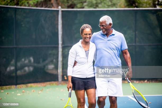 senior black couple on tennis court - active lifestyle stock pictures, royalty-free photos & images