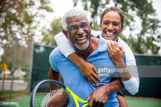 senior black couple on tennis court piggyback - coppia anziana foto e immagini stock