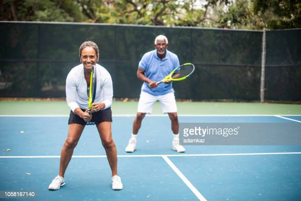 senior black couple playing doubles tennis - doubles stock pictures, royalty-free photos & images