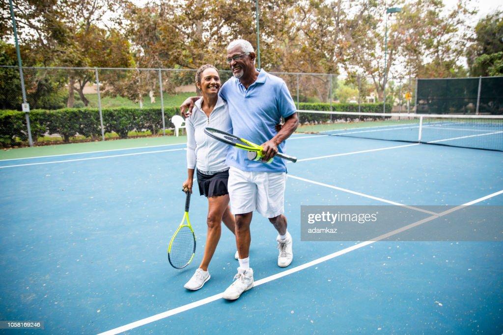 Senior Black Couple Walking Off the Tennis Court : Stock Photo