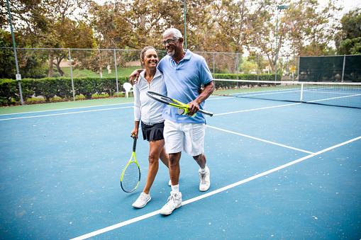 Senior Black Couple Walking Off the Tennis Court 1058169246