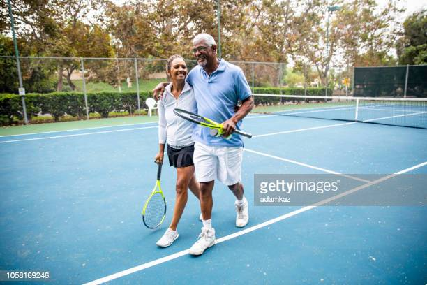 senior black couple walking off the tennis court - mature adult stock pictures, royalty-free photos & images