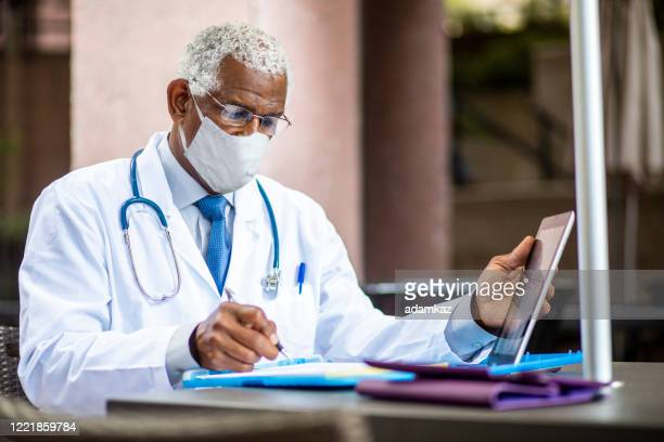 senior black doctor filing a report wearing a mask - administrator stock pictures, royalty-free photos & images