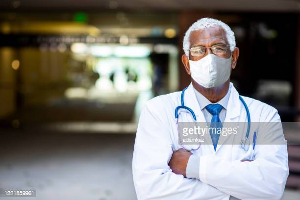 senior black male doctor portrait at hospital wearing mask - adamkaz stock pictures, royalty-free photos & images