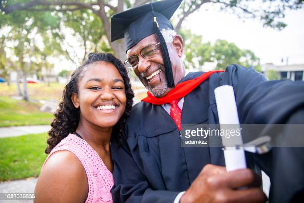senior black man at graduation taking a selfie with his daughter - master's degree stock pictures, royalty-free photos & images
