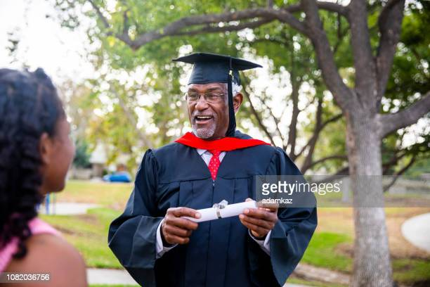 senior black man at graduation talking with his family - master's degree stock pictures, royalty-free photos & images