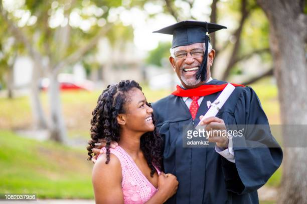 senior black man at graduation with his daughter - master's degree stock pictures, royalty-free photos & images