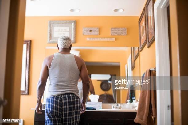 Senior schwarzer Mann immer bereit im Badezimmer