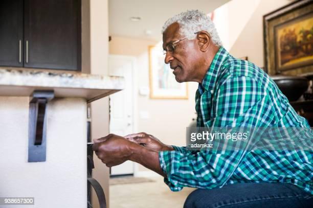 senior black man home repairs - adjusting stock pictures, royalty-free photos & images