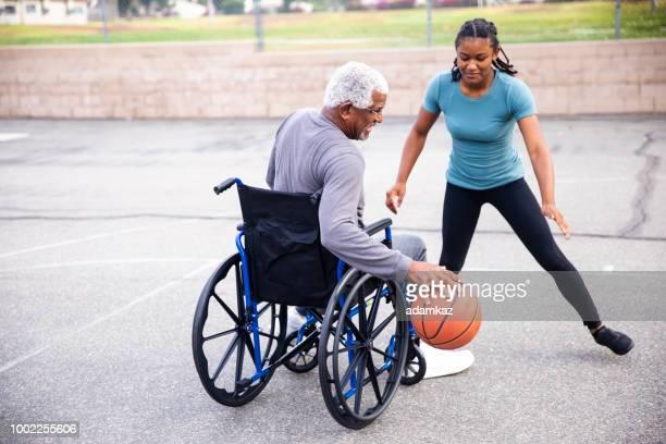 Senior Black Man in Wheelchair dribbling basketball