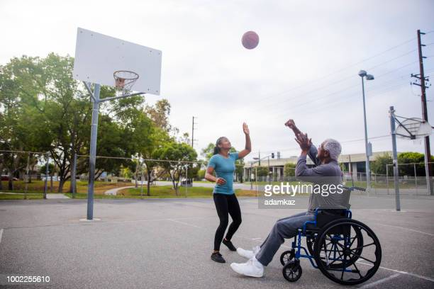 senior black man in wheelchair shooting basketball - showing respect stock pictures, royalty-free photos & images