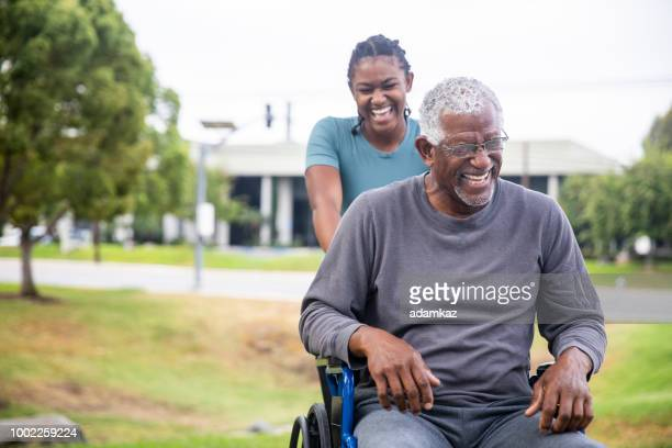 senior black man in wheelchair with daughter - caregiver stock pictures, royalty-free photos & images