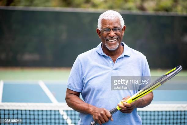 senior black man playing tennis - tennis racket stock pictures, royalty-free photos & images